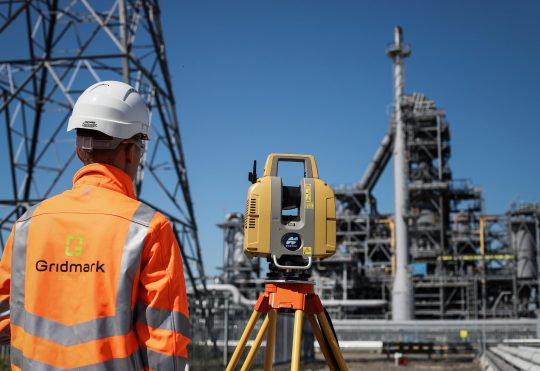 a surveyor surveying an industrial site